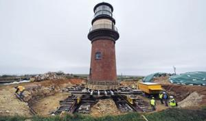 A worker climbs out of a hole dug around the Gay Head Lighthouse while moving the historic structure in Aquinnah, Mass., on the island of Martha's Vineyard, Thursday, May 28, 2015. The 160-year-old lighthouse started a multi-day trek to a new home slightly further inland.   The $3 million effort to move and save the structure was due to fear that it could tumble down a rapidly-eroding cliffside. (ANSA/AP Photo/Charles Krupa)